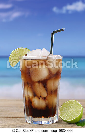Cola in glass with lime on the beach - csp19834444