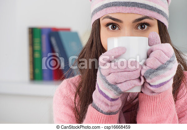 Cold and flue. Beautiful young woman in hat and gloves drinking tea while sitting at home - csp16668459