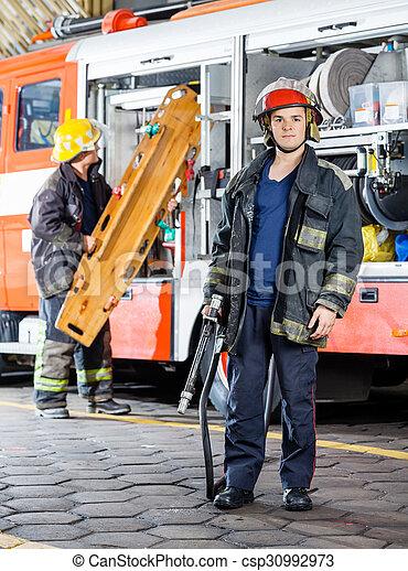 Bombero sosteniendo manguera mientras un colega lleva camilla - csp30992973