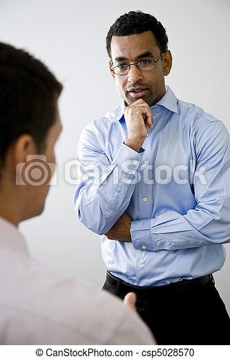 Trabajador de oficina de mediana edad escuchando a colega - csp5028570