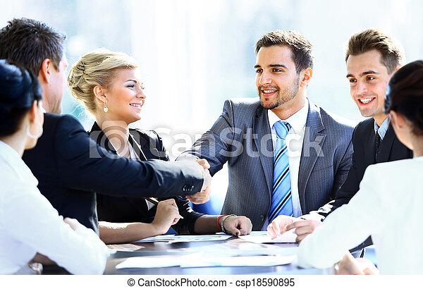 Colegas de negocios sentados en una mesa durante una reunión con dos ejecutivos dándose la mano - csp18590895