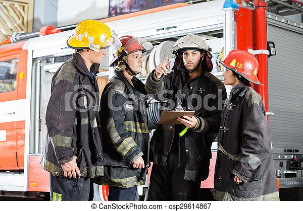 Bombero mostrando algo a colegas en la estación de bomberos - csp29614867