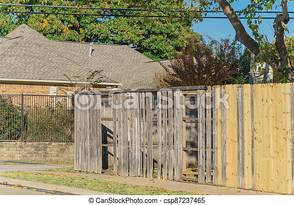 Collapsed aged wooden fence near new lumber boards installation at suburban house in Texas, USA - csp87237465
