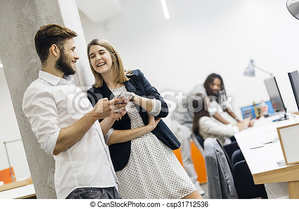 Colleagues in office using phones and smiling - csp31712536