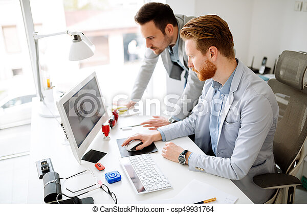 Colleagues working in office - csp49931764