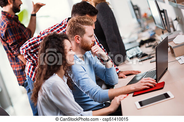 Colleagues working together in company office - csp51410015