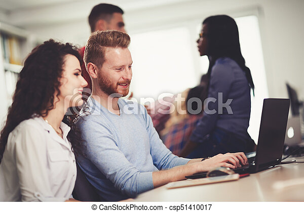 Colleagues working together in company office - csp51410017