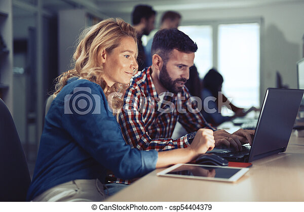 Colleagues working together in company office - csp54404379