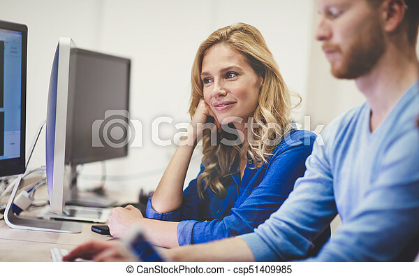 Colleagues working together in company office - csp51409985