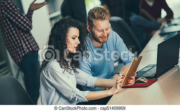 Colleagues working together in company office - csp51409959