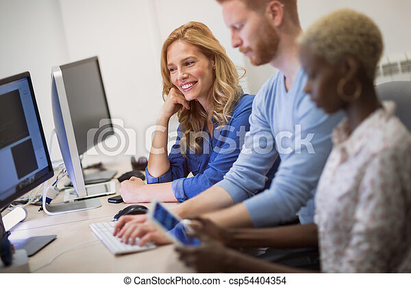 Colleagues working together in company office - csp54404354