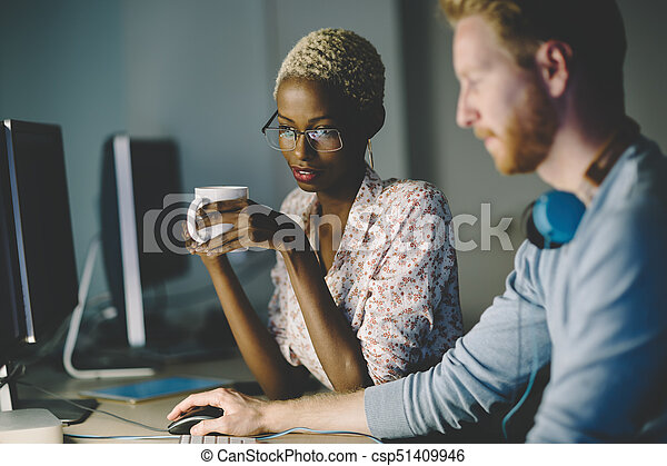 Colleagues working together in company office - csp51409946