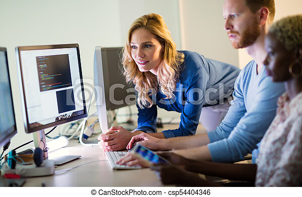 Colleagues working together in company office - csp54404346