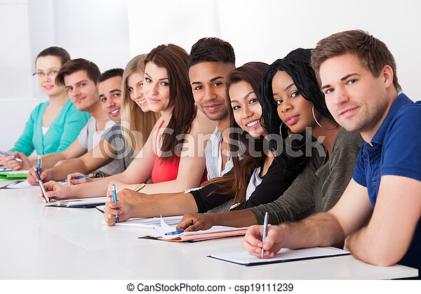 College Students Sitting In A Row At Desk - csp19111239