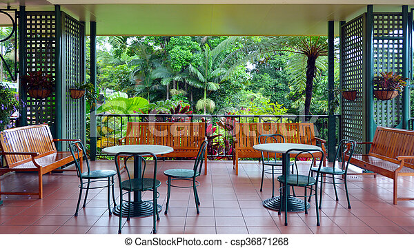 Colonial furnitures on a balcony against a tropical rain forest view - csp36871268