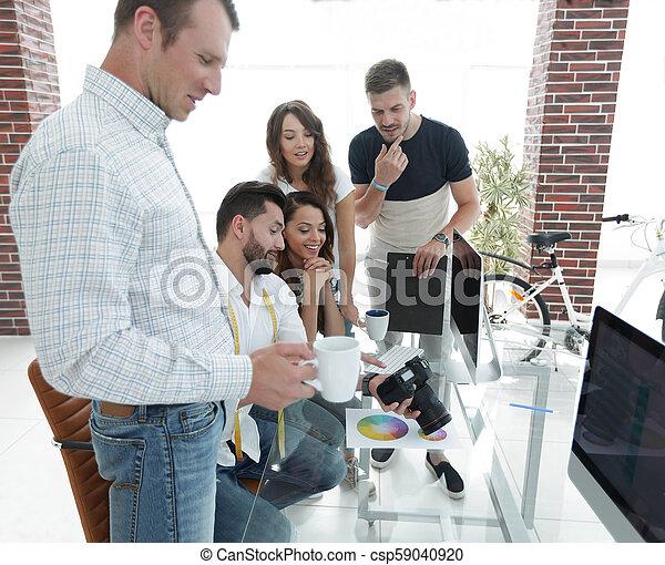 Fotógrafo y colegas discutiendo la paleta de color - csp59040920