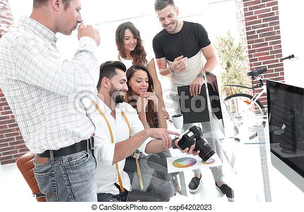 Fotógrafo y colegas discutiendo la paleta de color - csp64202023