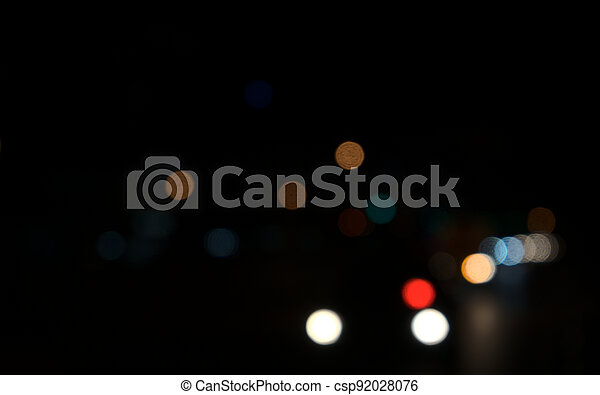 Colored circles bokeh of car lights at black dark night in city. Blurry abstract texture background. - csp92028076