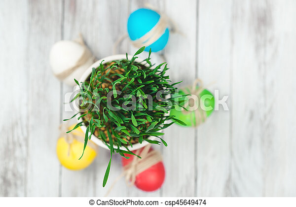Colored easter eggs, flower pot with green grass on wooden background. Top view. - csp45649474