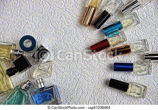 Colored glass bottles with perfume on a gray table - csp51236464