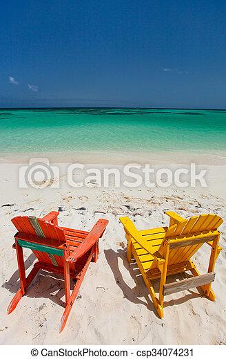 Colorful adirondack lounge chairs at Caribbean beach - csp34074231