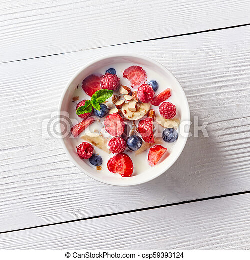 Colorful and tasty ready breakfast from corn muesli, berries, milk, almonds, slices banana on a bowl on a white wooden table with copy space. Flat lay. - csp59393124