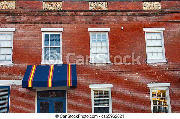 Colorful Awning Over Blue Door On An Old Brick Building Stock Photo