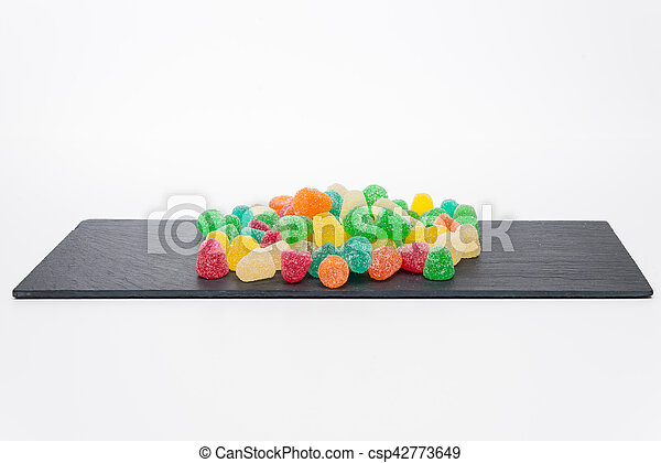 Colorful candy on a dark stone background - csp42773649
