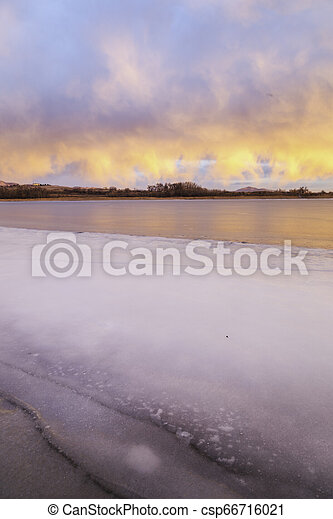 Colorful Clouds over a frozen Colorado Lake - csp66716021