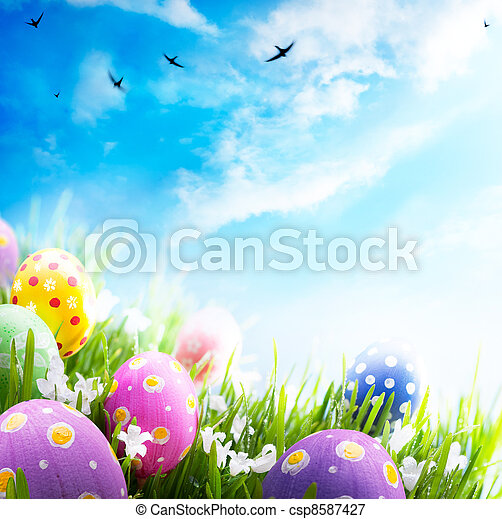 Colorful Easter eggs decorated with flowers in the grass on blue sky background - csp8587427
