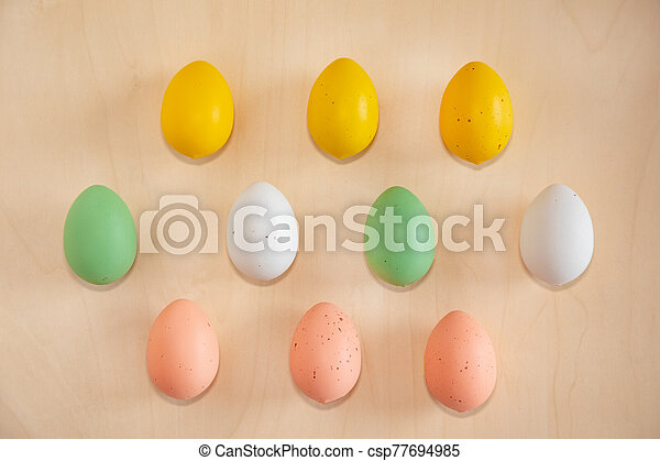 Colorful easter eggs on wooden background - csp77694985
