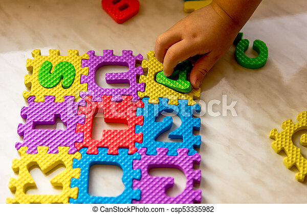 Colorful foam puzzle letters and numbers in kid's hands on a light table - csp53335982