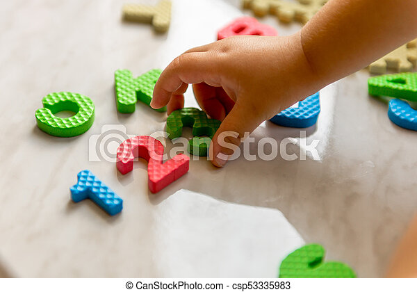 Colorful foam puzzle letters and numbers in kid's hands on a light table - csp53335983