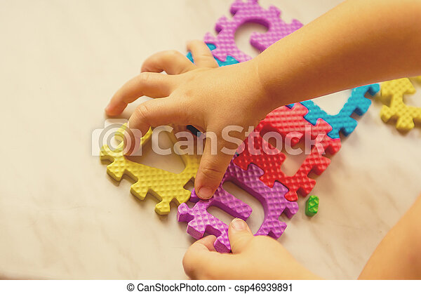 Colorful foam puzzle letters and numbers in kid's hands on a light table - csp46939891