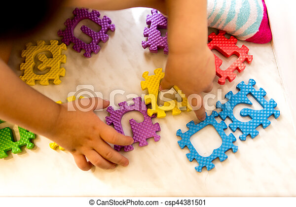 Colorful foam puzzle letters and numbers in kid's hands on a light table - csp44381501