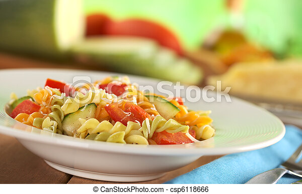 Colorful fusilli pasta with zucchini, tomato and grated cheese with fork on the side and ingredients in the back (Selective Focus, Focus one third into the meal) - csp6118666