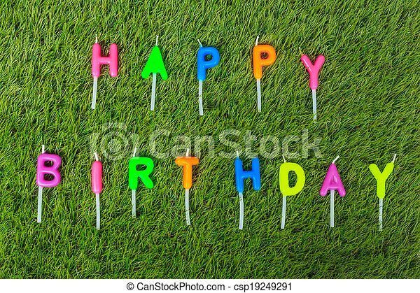 Colorful happy birthday candles on field - csp19249291