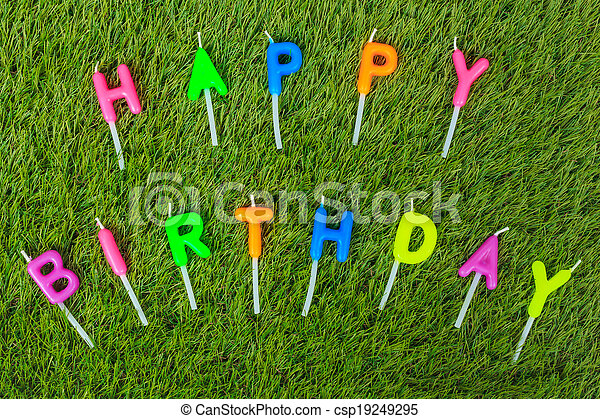 Colorful happy birthday candles on field - csp19249295