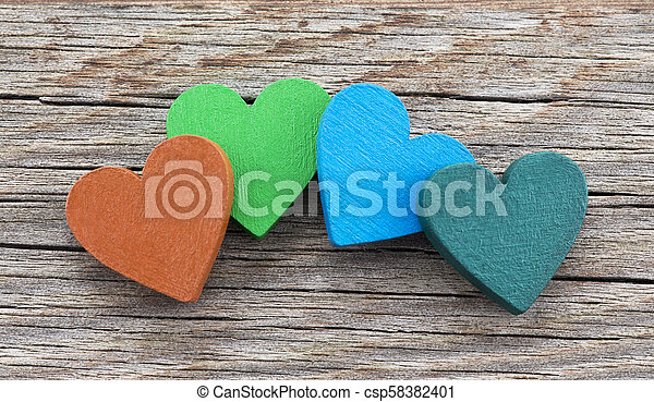 Colorful hearts on wooden background - csp58382401