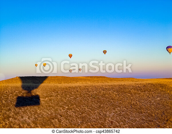 Colorful hot air balloons flying over the valley at Cappadocia - csp43865742