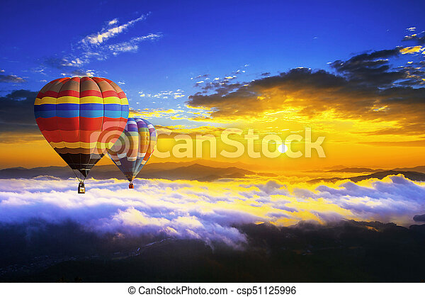 Colorful hot air balloons flying over the mountain covered by morning fog at sunrise. - csp51125996