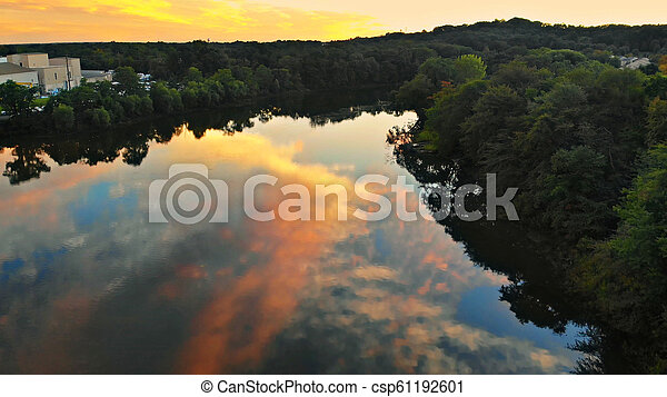 Colorful landscape of river near a forest under a beautiful sky with bright clouds during sunset - csp61192601