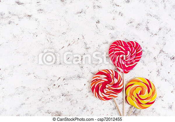 Colorful lollipops on white background. Top view - csp72012455
