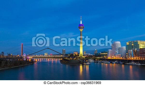 Colorful night scene of Rhein river at night in Dusseldorf. Rheinturm tower in the soft night light, Nordrhein-Westfalen, Germany, Europe. - csp36631969