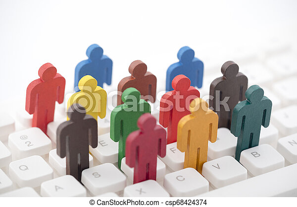 Colorful painted group of people figures on computer keyboard - csp68424374