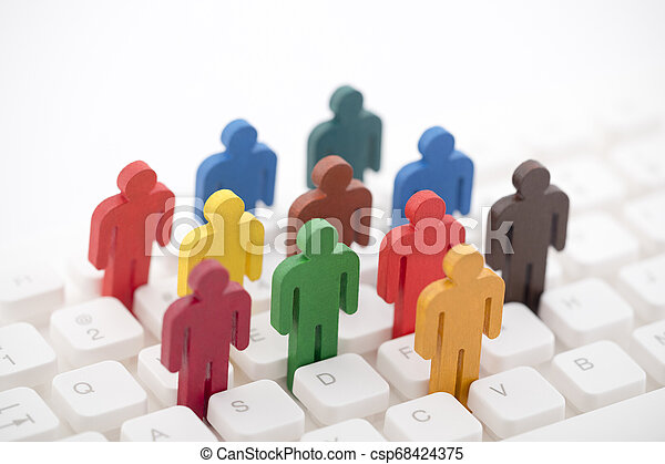 Colorful painted group of people figures on computer keyboard - csp68424375