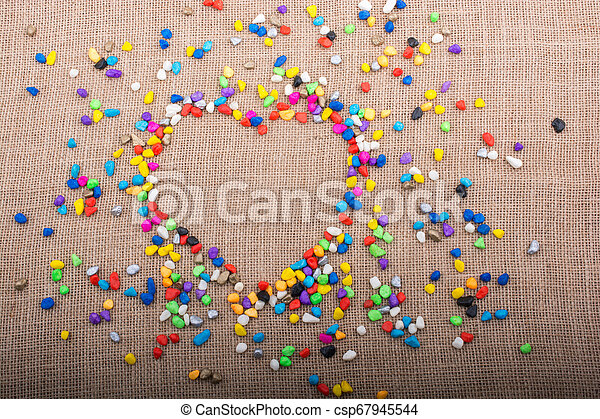Colorful pebbles form a heart shape on canvas ground - csp67945544