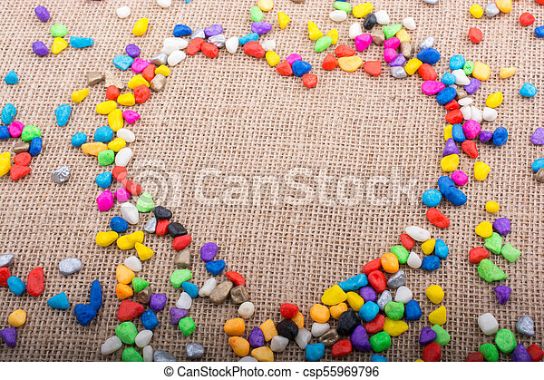 Colorful pebbles form a heart shape on canvas ground - csp55969796