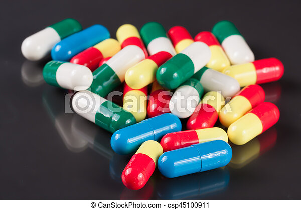 colorful pills on a dark background - csp45100911
