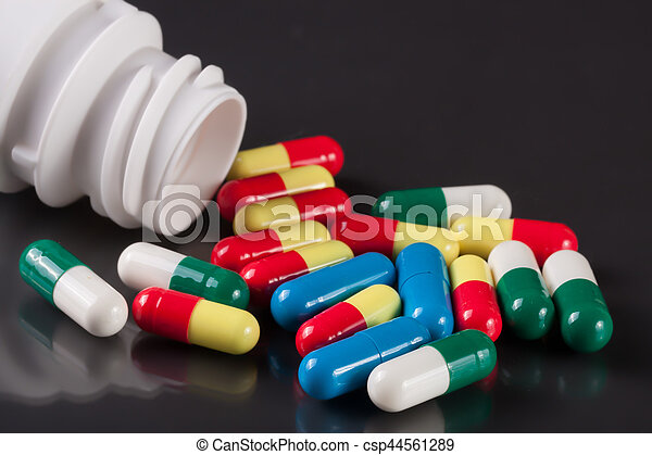colorful pills on a dark background - csp44561289